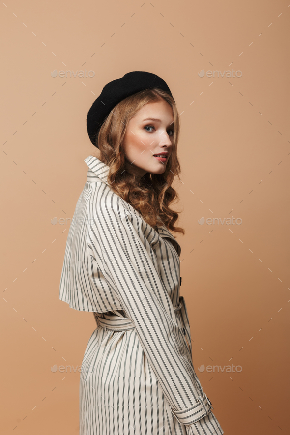 Young pretty lady with wavy hair in striped coat and black hat dreamily looking in camera - Stock Photo - Images
