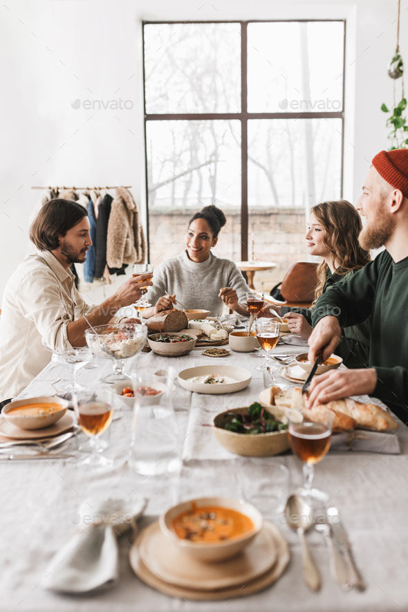 Group of beautiful international friends sitting at the table full of food talking to each other - Stock Photo - Images