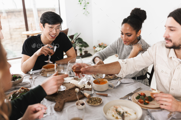 Group of attractive international friends sitting at the table full of food happily eating together - Stock Photo - Images