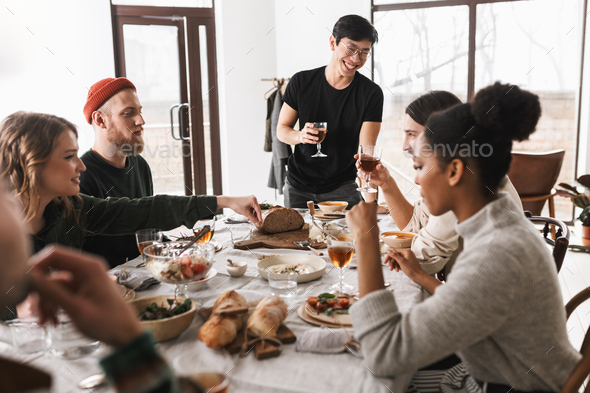 Young cheerful asian man in eyeglasses and black T-shirt holding glass of wine saying toast - Stock Photo - Images