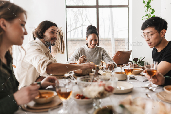 Young colleagues happily discussing work having lunch together - Stock Photo - Images