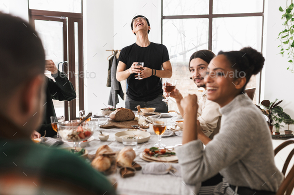 Group of attractive international friends joyfully spending time together on lunch in cozy cafe - Stock Photo - Images
