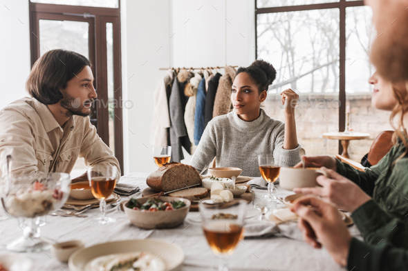 African american woman sitting at the table thoughtfully looking at man with beard - Stock Photo - Images