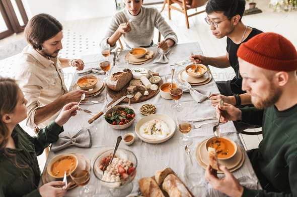 Top view of attractive international friends sitting at the table full of food eating together - Stock Photo - Images