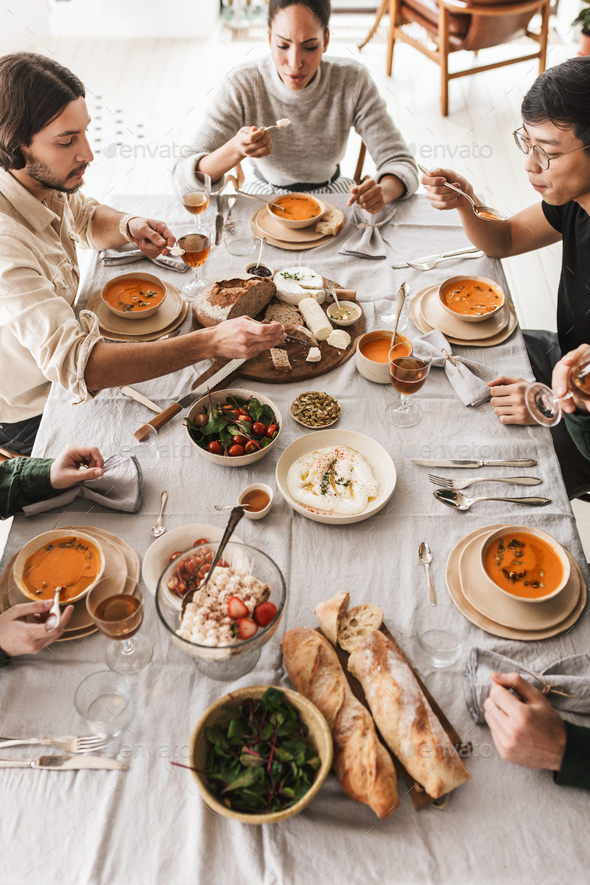 Top view of international friends sitting at the table full of food dreamily eating together - Stock Photo - Images