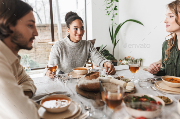 Pretty smiling african american woman sitting at the table full of food dreamily looking friend - Stock Photo - Images