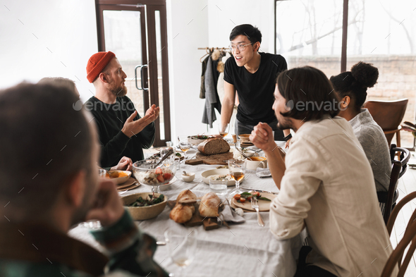 Young asian man in eyeglasses and black T-shirt leaning on table happily talking with colleagues - Stock Photo - Images