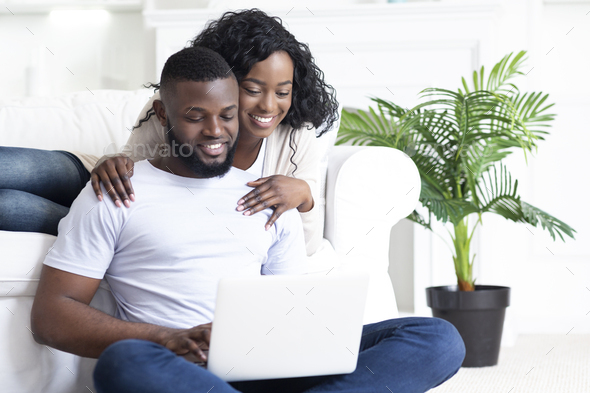 Happy young african american couple using portable pc at home - Stock Photo - Images