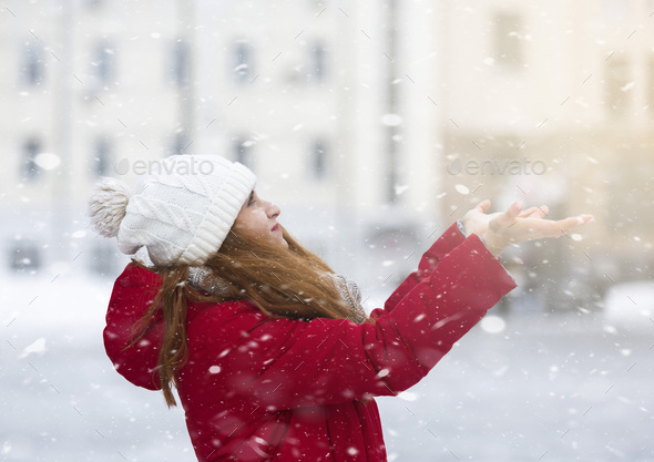Young woman playing with snowflakes over city background - Stock Photo - Images