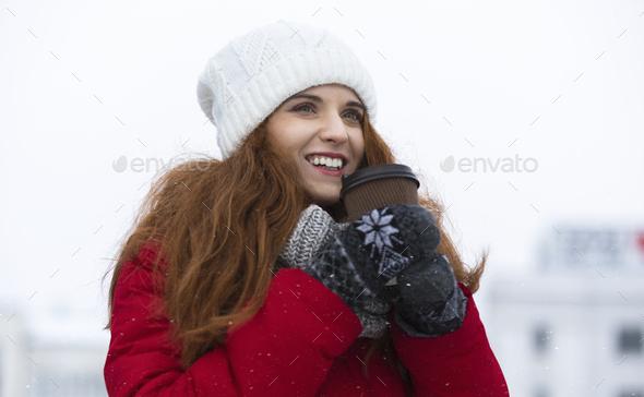 Beautiful ginger girl enjoying hot drink on winter day - Stock Photo - Images