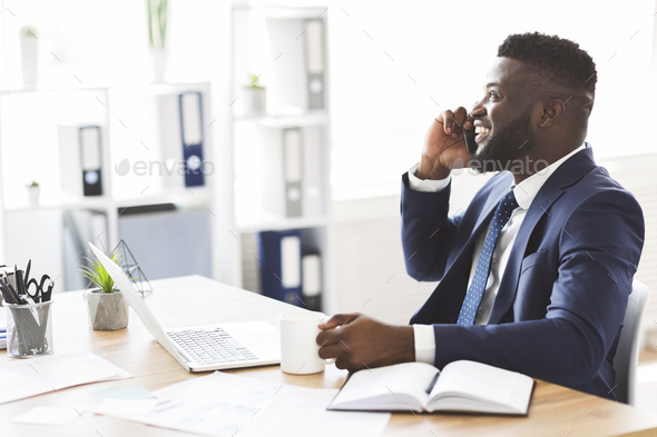 Black businessman talking on mobile phone, drinking coffee at office - Stock Photo - Images