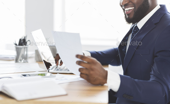 Cropped photo of happy african entrepreneur looking at documents - Stock Photo - Images