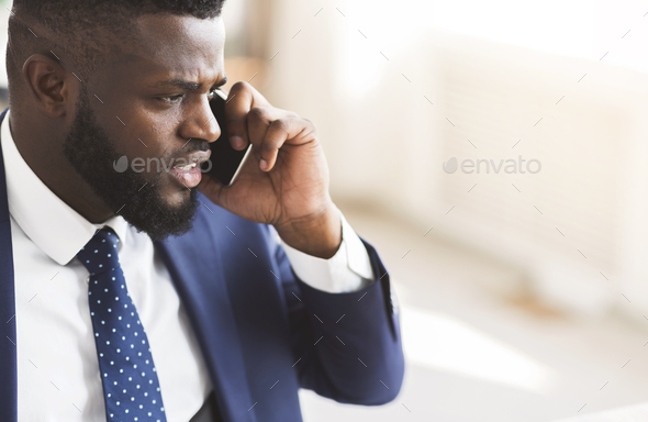 Furious businessman talking by smartphone with partners - Stock Photo - Images