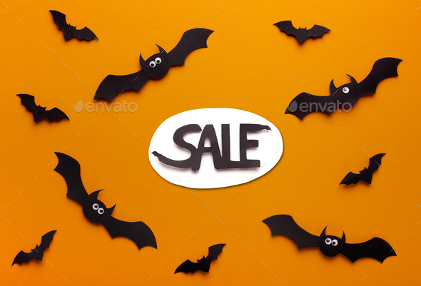 Flying paper bats on orange background with promo text - Stock Photo - Images