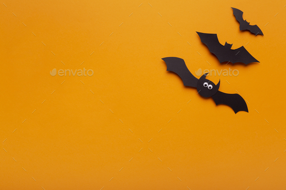 Black paper bats on orange background with copy space - Stock Photo - Images