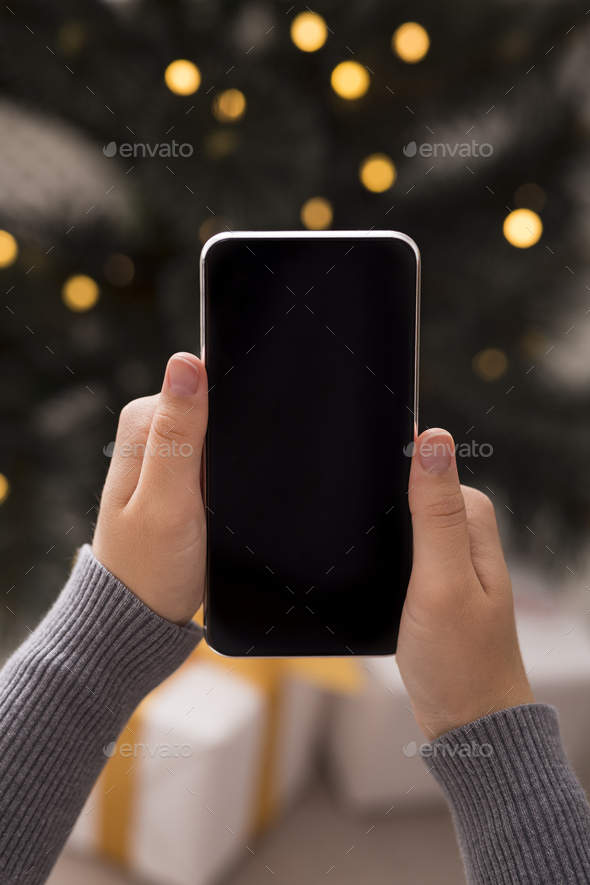 Cellphone in woman hands in over Christmas background - Stock Photo - Images
