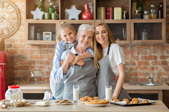 Female family taking photo while cooking together - Stock Photo - Images