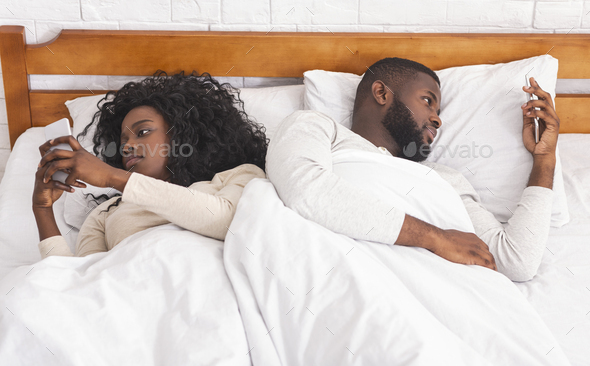Couple ignoring each other after argue, using smartphones in bed - Stock Photo - Images