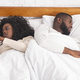 Couple ignoring each other after argue, using smartphones in bed - PhotoDune Item for Sale