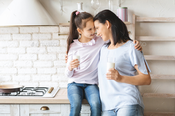Mother and daughter drinking milk in kitchen and touching foreheads - Stock Photo - Images
