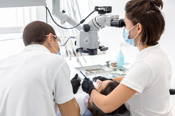 Back view of dentist doctors making dental cleaning - Stock Photo - Images