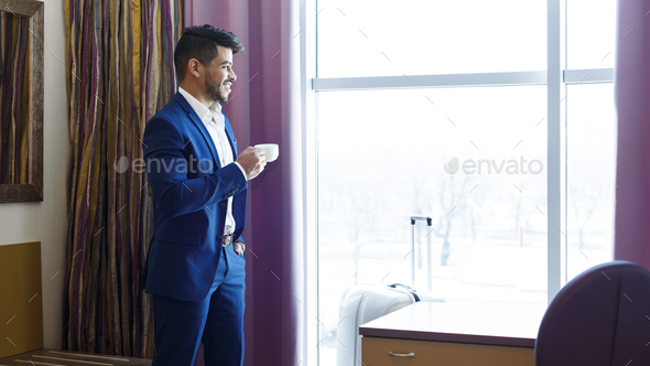 Handsome man in suit drinking coffee near window in hotel - Stock Photo - Images