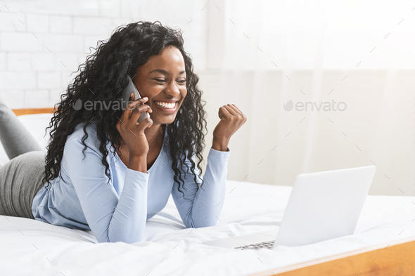 Excited young woman got job, talking by phone in bedroom - Stock Photo - Images