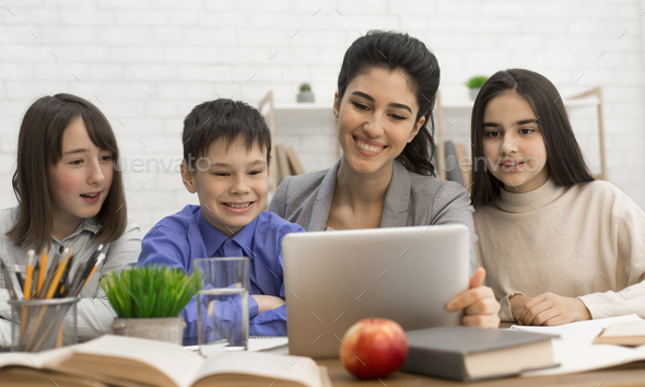 Young teacher showing children tutorials online on tablet - Stock Photo - Images