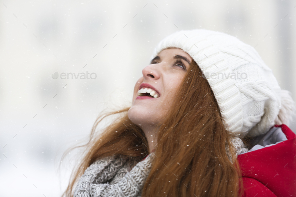 Joyful ginger girl in winter clothes looking up - Stock Photo - Images