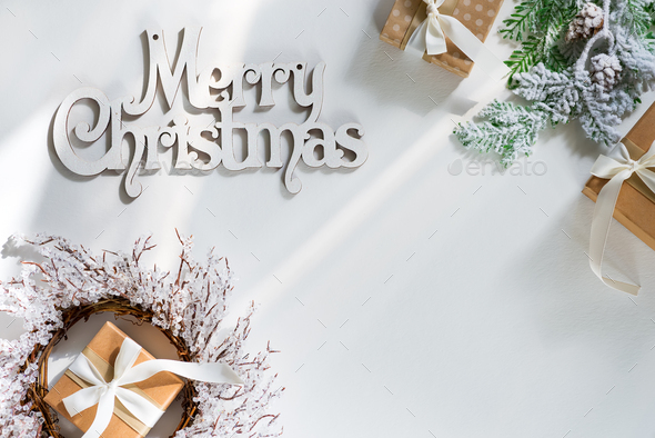 Gift boxes with snow fir branches, Wooden letters Merry Christmas and sunlight rays on a white - Stock Photo - Images