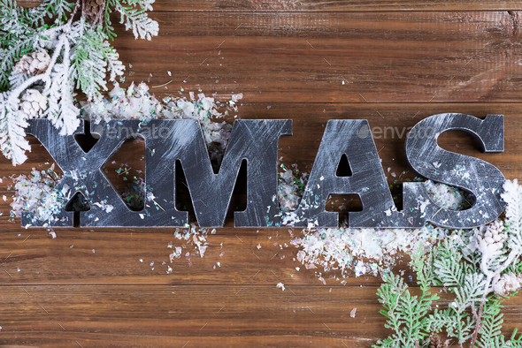 Wooden letters XMAS with fit branches and snow on a wooden background. Christmas card. Flat lay - Stock Photo - Images