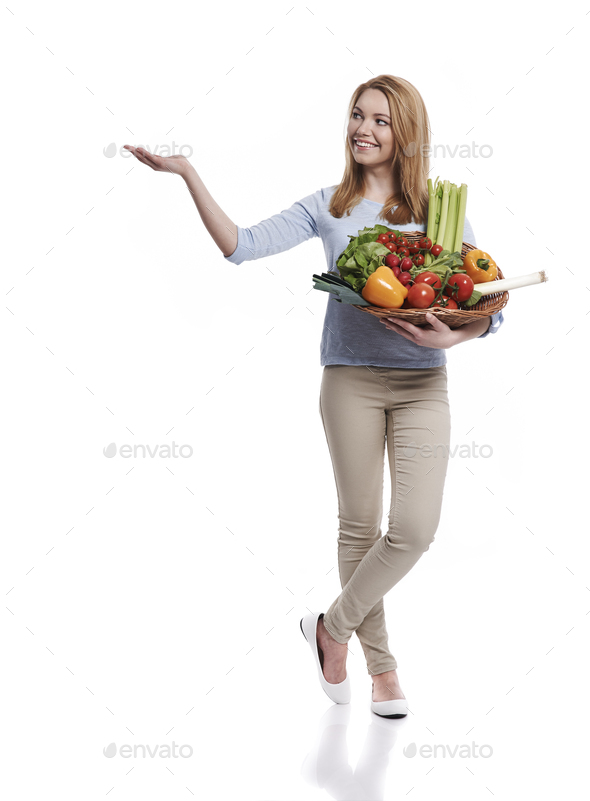 Woman with basket full of healthy food showing on copy space - Stock Photo - Images