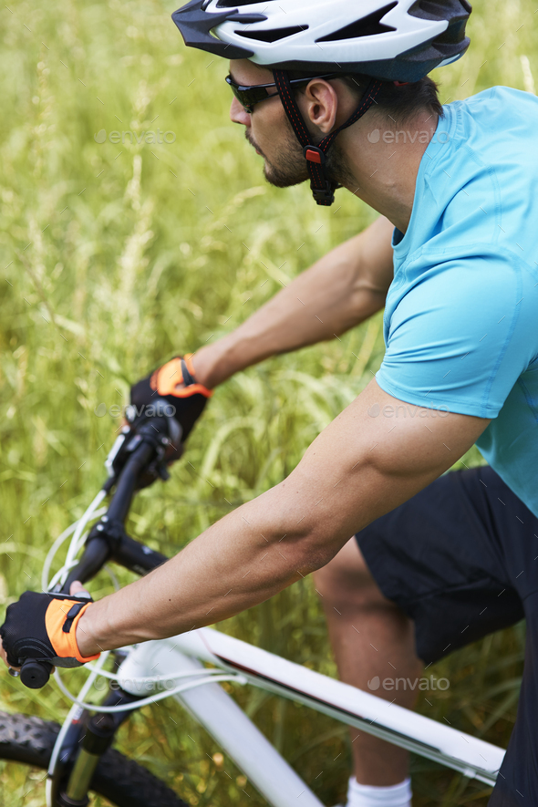 Man cycling across the meadow - Stock Photo - Images