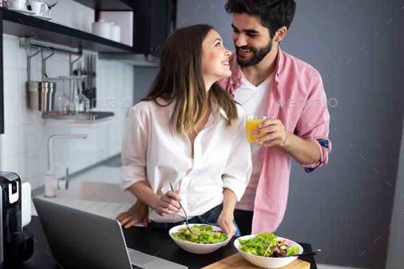 Beautiful young playful couple eating salad together at home - Stock Photo - Images