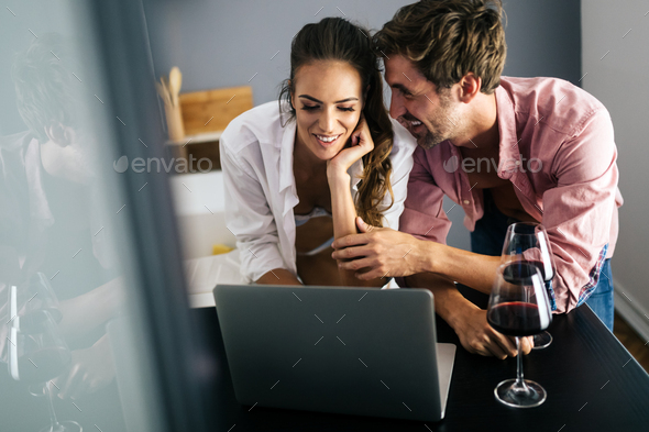 Happy smiling couple using laptop at home - Stock Photo - Images