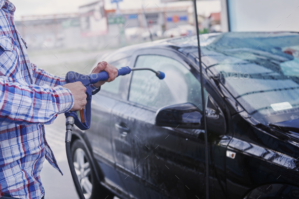 Washing a car with spray water - Stock Photo - Images