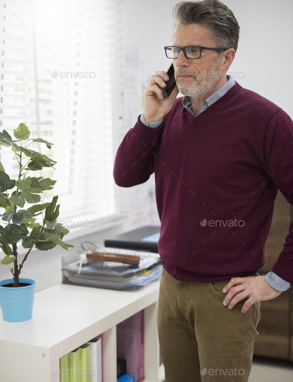 Boss talking on the phone next to the window - Stock Photo - Images
