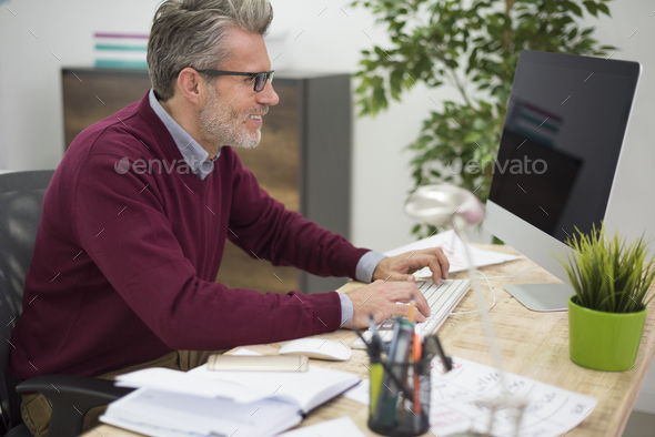 Affectionate man working on his computer - Stock Photo - Images