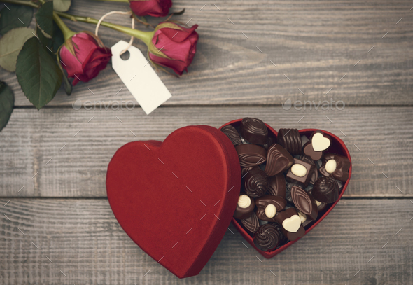 Roses and opened chocolate box - Stock Photo - Images