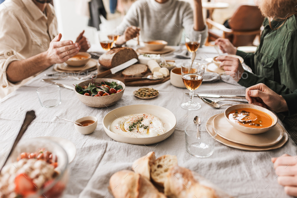 Group of young people sitting at the table full of delicious food and glasses of wine having lunch - Stock Photo - Images