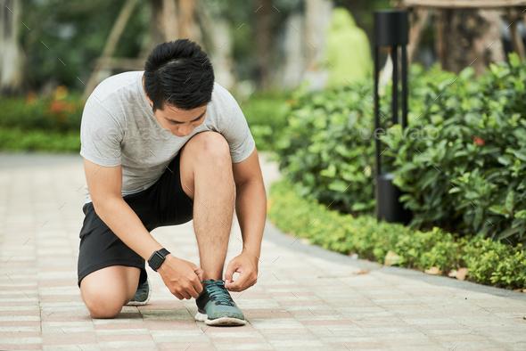 Sportsman tying shoe laces - Stock Photo - Images