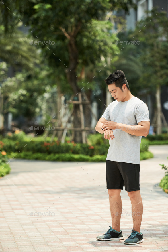 Sportsman checking smart watch - Stock Photo - Images
