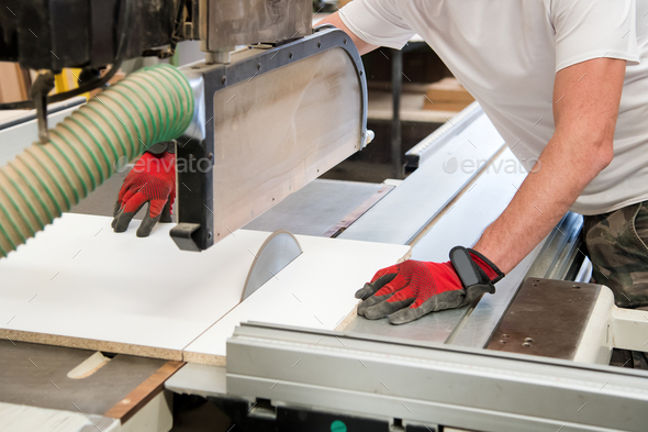 Carpenter or joiner cutting a wooden board - Stock Photo - Images