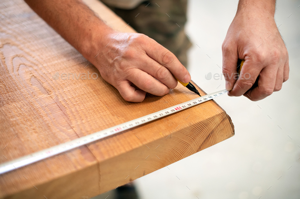 Carpenter measuring a wooden plank - Stock Photo - Images