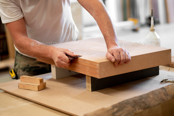 Carpenter sanding the edge of a wooden block - Stock Photo - Images