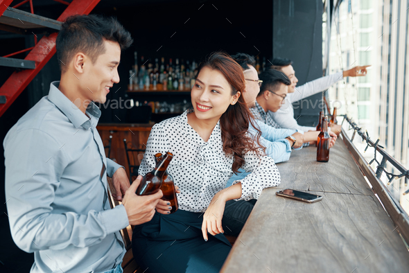 Young Asian couple flirting in bar - Stock Photo - Images