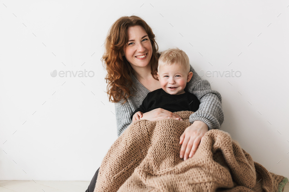 Young beautiful smiling mom with red hair in knitted sweater sitting on floor with her little son - Stock Photo - Images