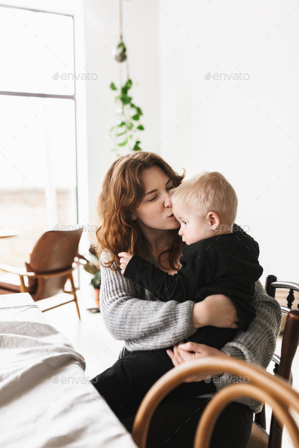 Young beautiful woman in knitted sweater dreamily kissing her little son - Stock Photo - Images