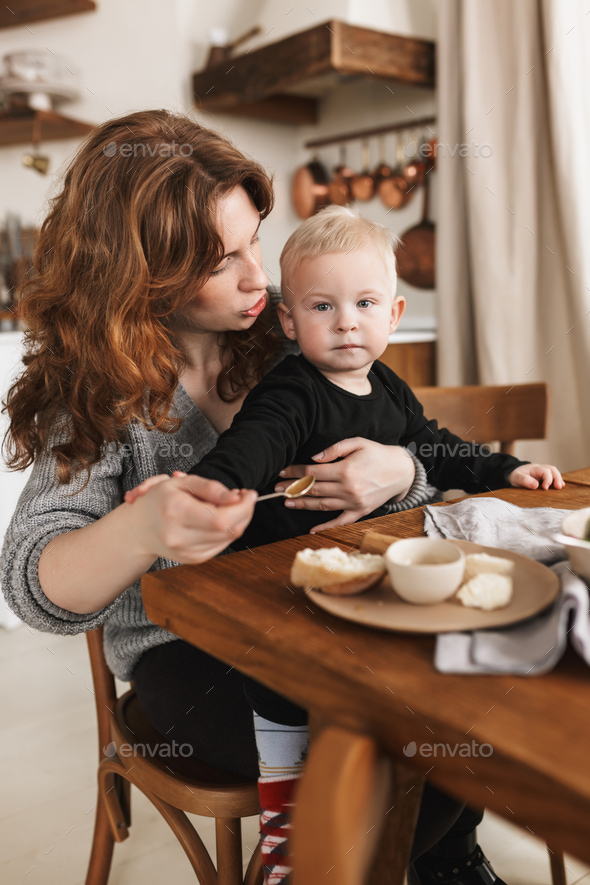 Young redhead woman in knitted sweater sitting at the table with food dreamily feeding her baby - Stock Photo - Images