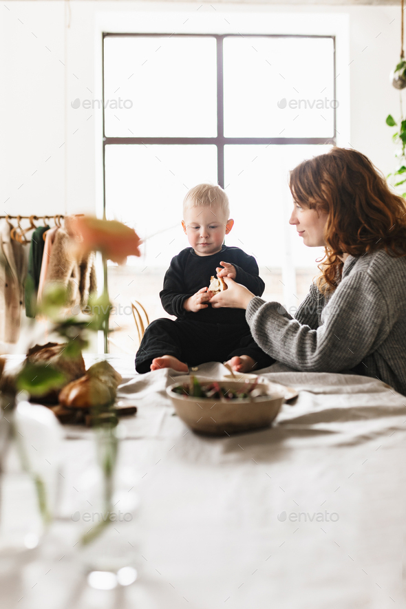 Young beautiful mom with red hair in knitted sweater dreamily playing with her little handsome son - Stock Photo - Images